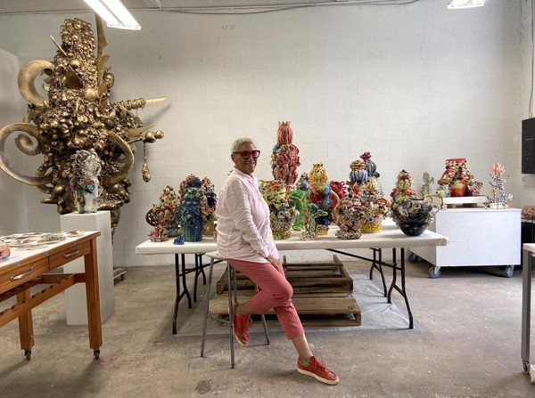 [1] Artist Charo Oquet posing in front of her work.png