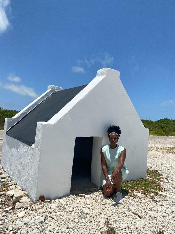 LS kneeling in front of slave hut.jpg
